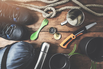 expedition camping equipment on wooden plank background. top view