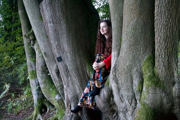 Fashionable lady sitting in a beech tree