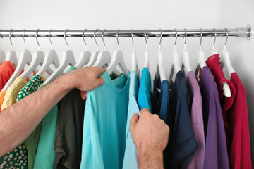 Man choosing clothes from rack in wardrobe, closeup