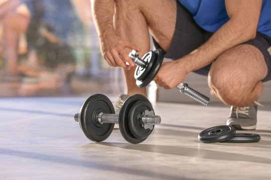 Male athlete with adjustable dumbbells indoors. Space for text