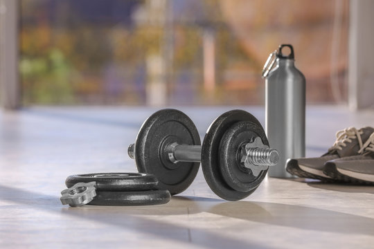 Adjustable dumbbell with parts, bottle and sneakers on floor indoors. Space for text