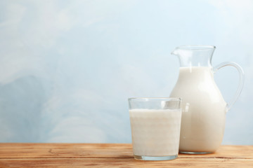 Glass and jug of fresh milk on wooden table against color background. Space for text