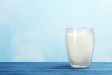Glass with fresh milk on table against color background. Space for text