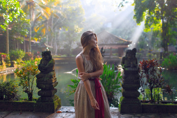 Beautiful girl in the morning in a Buddhist temple. Tropical Garden in Asia