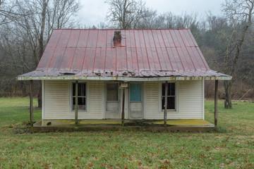 Old duplex farmhouse in grass field