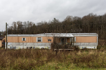 Abandoned mobile home with orange and white trim surrounded by overgrown grass