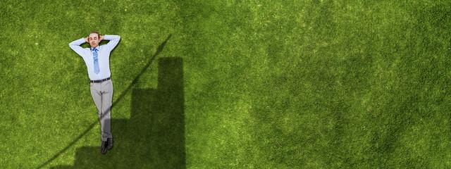 Relaxing businessman on grass