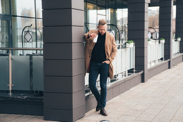 Attractive man in trendy brown coat and coffe in his hand posing near business center