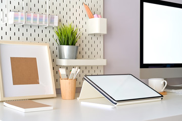 Home office desk scenery with mockup blank screen tablet and desktop computer. Workspace minimal