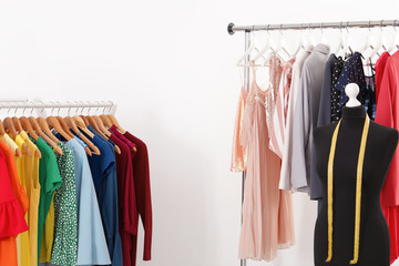 Racks with collection of trendy clothes on white background. Stylist's workplace