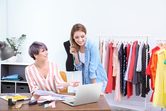 Young clothes stylist speaking with customer at workplace