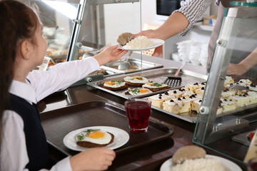 Woman giving plate with healthy food to girl in school canteen