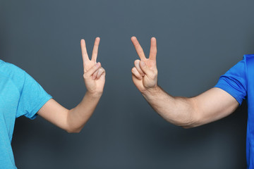 Man and woman showing victory gestures on color background