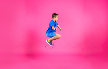 Active boy jumping rope on color background