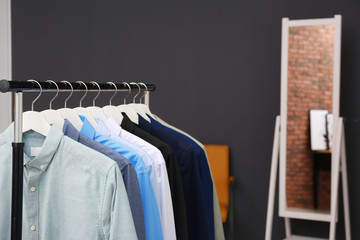 Wardrobe rack with stylish clothes in dressing room. Space for text