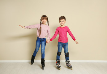Cute boy and girl with roller skates near color wall