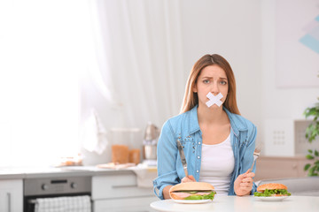 Emotional young woman with taped mouth and burgers at table in kitchen. Healthy diet