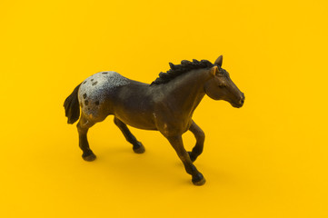 Toy horse made of plastic on a yellow background.