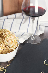 egg noodles and a glass of red wine and a place for text.