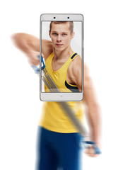 Photo of concentrated young sporty man working out with expander. conceptual image with a smartphone, demonstration of device capabilities