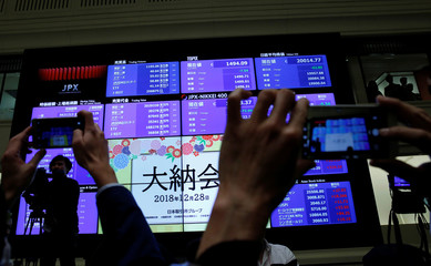 Attendees take pictures of a stock quotation board after a ceremony marking the end of trading in 2018 at the Tokyo Stock Exchange (TSE) in Tokyo