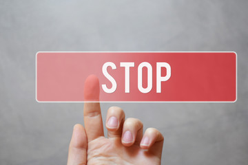 Stop - hand pressing red transparent button on virtual touchscreen interface on grey background with copy space. Emergency stop for safety.