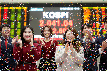 Employees of the Korea Exchange (KRX) pose in front of the final stock price index during a photo opportunity for the media at the ceremonial closing event of the 2018 stock market in Seoul