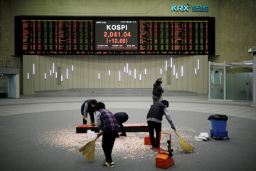 Workers sweep the floor after a photo opportunity for the media at the ceremonial closing event of the 2018 stock market in Seoul