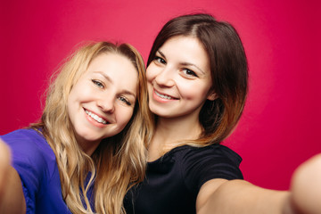 Self portrait of two beautiful, positivity girls, taking photo,smiling and posing together. Happy emotionally women with hairstyles,makeup, using camera at studio. Woman s friendship. Pink background.