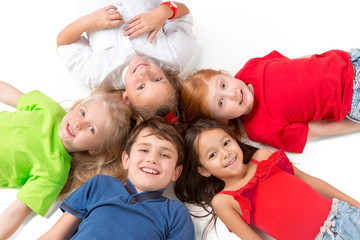 Close-up of happy children lying on floor in studio and looking up, isolated on white background, top view. Kids emotions and fashion concept