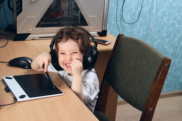 Little 2 3 year old baby girl in white clothers draws at the home computer in graphics drawing tablet. The child is holding a pen and laughs. On the head are huge headphones