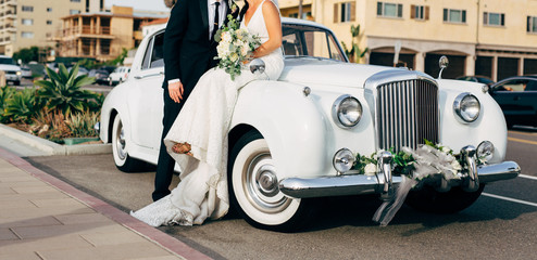 bride and groom next to classic car on street kissing
