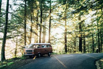 classic van sitting on side of road at sunset in forest