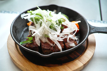 grilled beef steak served in an iron pan with sliced onion