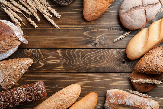 Freshly baked bread products on wooden background, top view