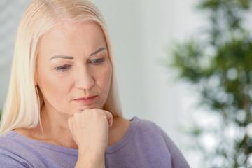 Portrait of sad mature woman at home