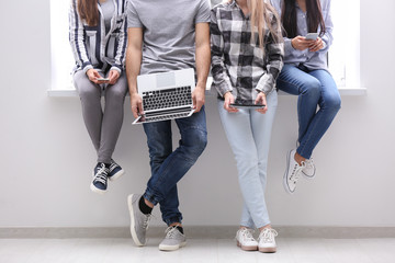 Young people with modern devices near window indoors