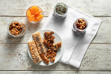 Plate with tasty baked granola and bars on wooden background