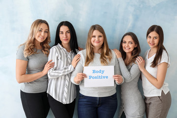 Beautiful young women holding paper sheet with text BODY POSITIVITY on color background