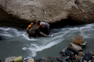 Men remove a rock in contaminated sewage water at an area known as 'the Mine', where informal workers search for scrap metal, at the largest garbage dump of Guatemala City
