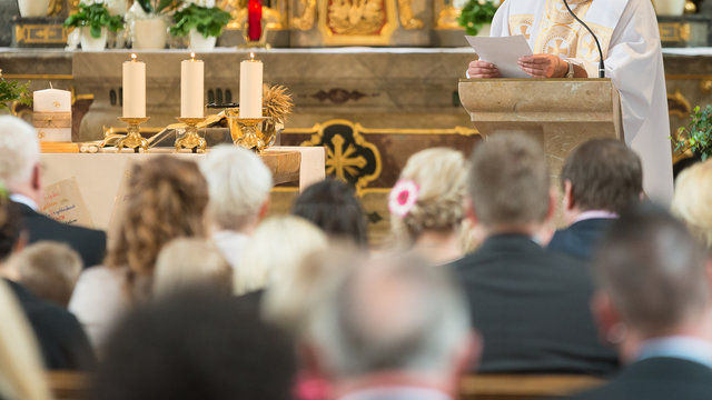 People with preacher are listen and Pray in a catholic church