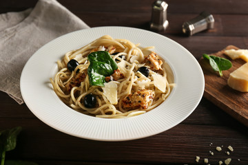 Tasty pasta with meat, olives and cheese on plate