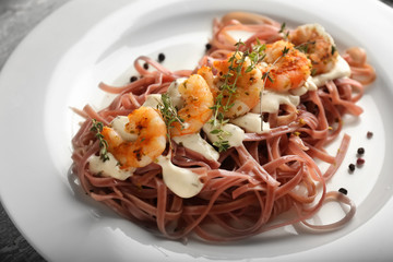 Plate of tasty color pasta with sauce and shrimps, closeup