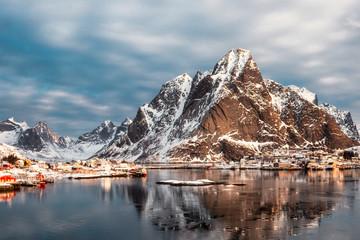 Snow mountain with scandinavian village on arctic ocean in winter