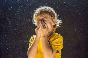 Allergy to dust. Boy sneezes because he is allergic to dust. Dust flies in the air backlit by light