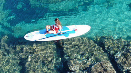 Aerial drone photo of fit woman dressed as Santa Claus on SUP or Stand Up Paddle surf board on tropical exotic sandy beach with turquoise sea