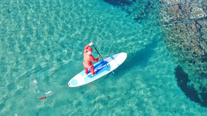Aerial photo of fit man dressed as Santa Claus practising SUP or Stand Up Paddle in exotic mediterranean beach with turquoise sea