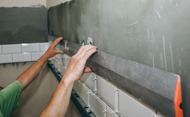 Man is putting white tiles on the grey concrete. Maintenance repair works renovation in the flat. Restoration with bubble level indoors. Work in process. Man is holding a spirit level in hands.