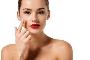 attractive girl with red lips applying cream on face and looking at camera isolated on white