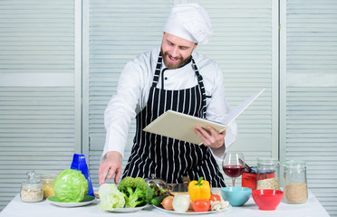 Improve cooking skill. Book family recipes. Ultimate cooking guide for beginners. According to recipe. Man bearded chef cooking food. Guy read book recipes. Culinary arts concept. Man learn recipe
